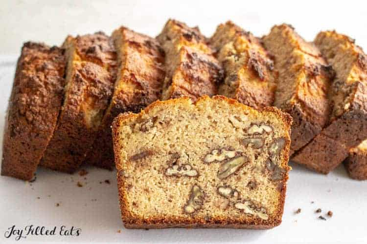 a slice of keto banana bread with nuts leaning on more slices
