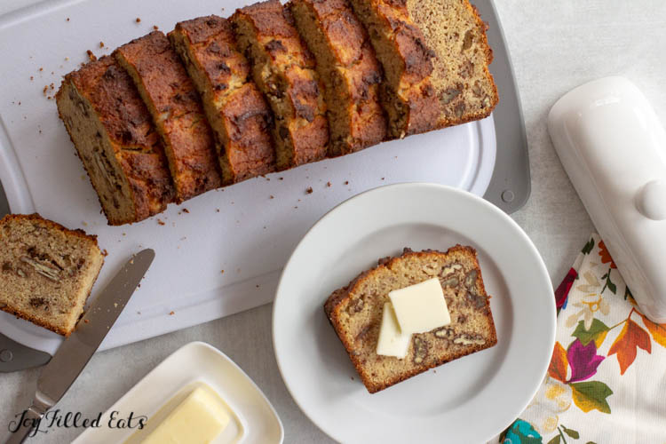 sliced banana bread with pecans on a cutting board with a piece on a small plate with butter