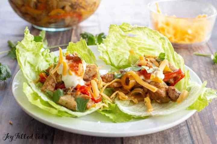lettuce on a white plate topped with baked chicken fajitas sour cream salsa and cheese