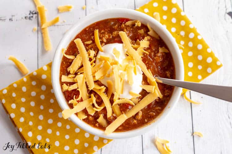 a white bowl of instant pot turkey chili with sour cream and cheese on top