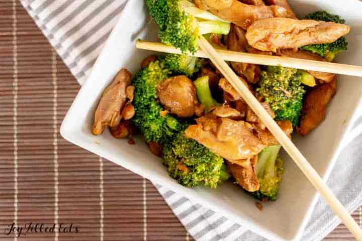 square bowl of stir fry chicken and broccoli with chopsticks
