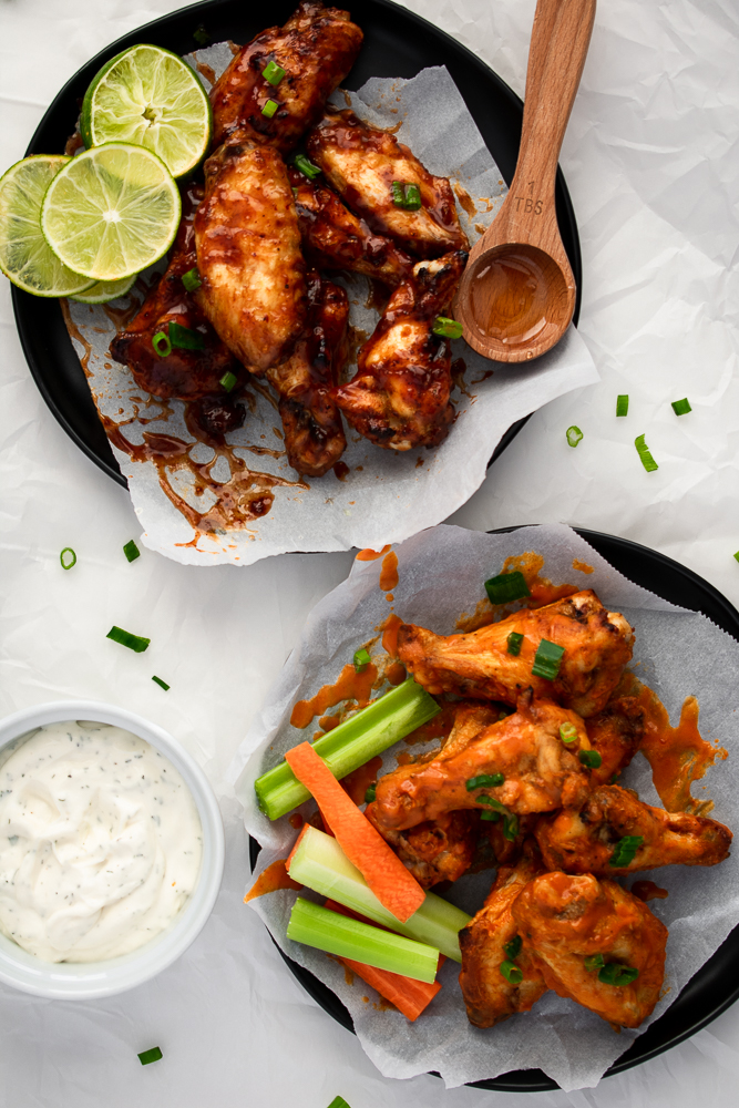 Oven baked chicken wings on a plate with classic buffalo sauce, honey chipotle bbq sauce and homemade ranch dressing
