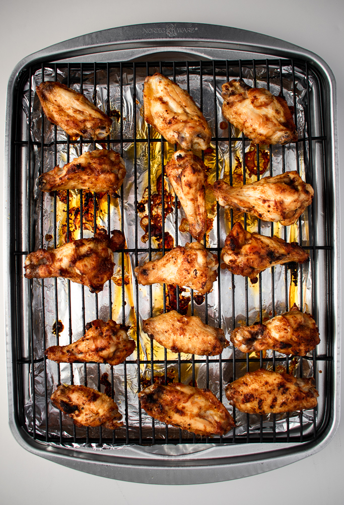 Baked chicken wings arranged on a baking sheet with a wire rack