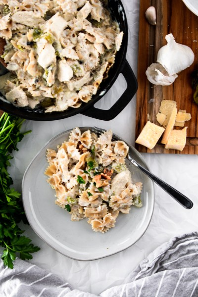 Colorado Green Chile Chicken Alfredo on a plate with ingredients on a cutting board