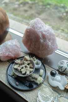 A large rose quartz crystal leans up against a window among other candles, herbs, and other supplies a spiritual healer might use. Joyful Empath offers spiritual therapy in Berkeley, CA, hsp therapy in Oakland, CA, and more. Contact us today to get in touch with a LGBTQ therapist in San Francisco, CA.
