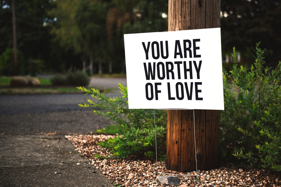 "A sign that reads ""you are worthy of love"" stands against a light pole on the shoulder of a road. An HSP therapist understands this, and can support you from our empaths refuge in Berkeley, CA. Reach out for more information on intuitive therapy, and more."