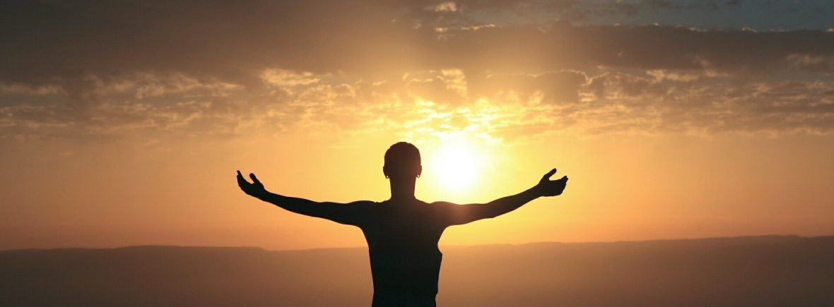 A silhouette of a person standing with their arms outstretched as they watch the sun set over the horizon. This could symbolize the feelings of freedom that come with being in tune with one's body. We offer somatic therapy in Berkeley, CA and other services. Contact a somatic therapist for support with somatic experiencing and more.
