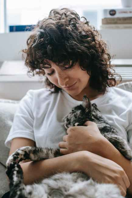 A smiling woman sits on sofa with a cat resting on her chest. The cat appears to be asleep, and both are relaxed. This could symbolize the comforting sensations that come with being in touch with one's body. We offer somatic therapy in Berkeley, CA. Contact a somatic therapist for support with somatic therapy today.
