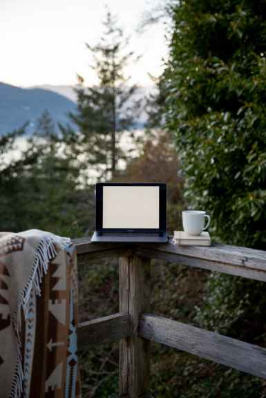 A laptop with a blank white screen rests on a balcony rail with tea, a blanket, and some books. The balcony overlooks a forest. Joyful Empath provides online therapy in san francisco, ca, and can help you feel safe and supported in your own space. Contact me today to get in touch with an online spiritual therapist in san francisco, ca, or online therapist in oakland, ca.