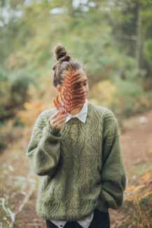 A person with their hair up in a messy bun, wearing a fuzzy green sweater, stands in a forest. They hold a fern of frond against their face. This symbolizse the peace and tranquility that comes from ecotherapy in Berkeley, CA. An eco therapist can support you in reconnecting with the world around you.