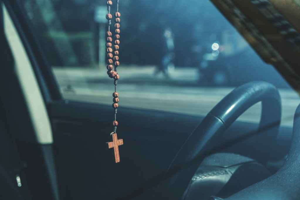 brown rosary dangling on car s rear view mirror