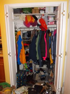 full coat closet with shoes spilling out into the hallway