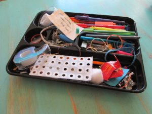 pens, tape, rubber bands, hole punch reinforcements tangled in messy desk drawer