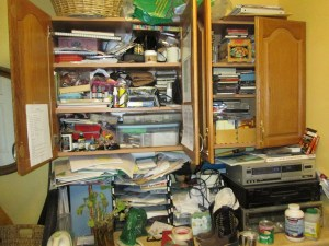 papers crammed into a cupboard above counter covered with clutter
