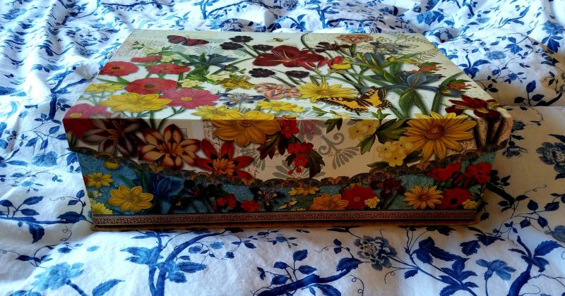 storage box decorated with colorful red and yellow flowers, on a blue and white patterned duvet cover