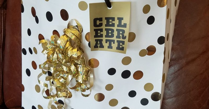 white and gold gift bag with gold ribbon and gift tag saying celebrate