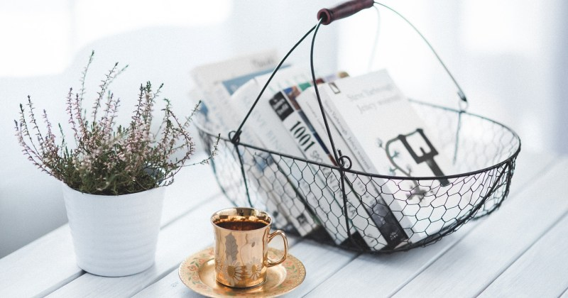 an organized desk with a sprig of lavender, an espresso cup and a wire basket organizing some books