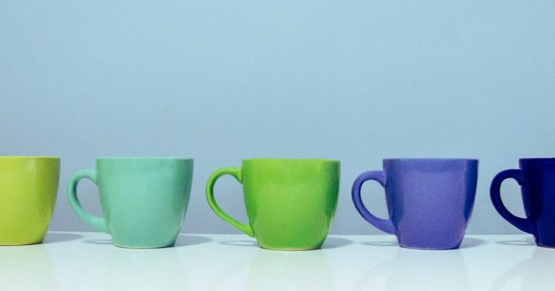 a row of colored cups (line green, seafoam, kelly green, sky blue, royal blue) on a light blue background
