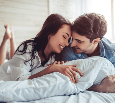 a young couple smiling and looking in love on top of a bed