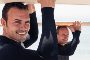 two men holding a surfboard on top of their heads