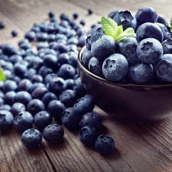 blueberries in a bowl and on a wooden table