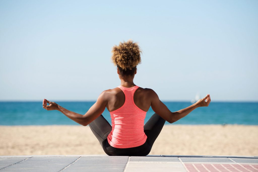 a young woman doing yoga on a beach and facing the ocean
