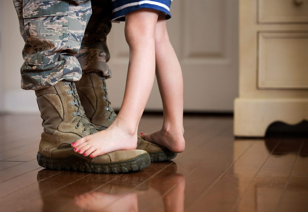 a child standing a soldier's boots