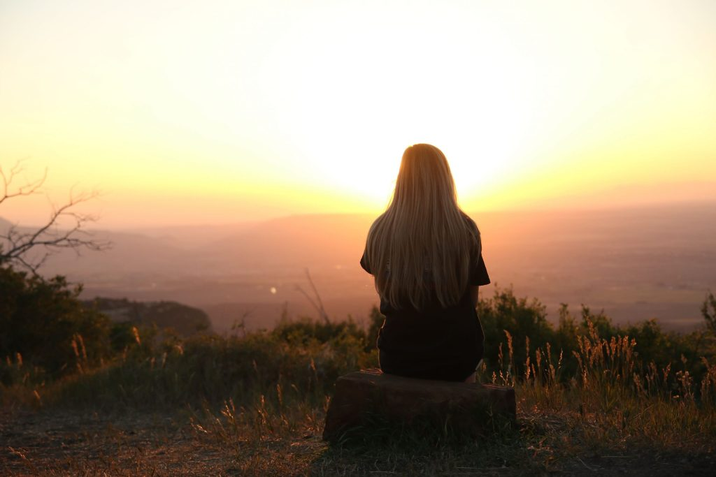 a woman with long blonde hair is sitting and admiring a sunset in a valley. Her back is towards the camera