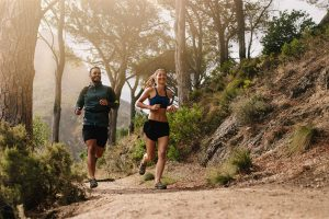 a young fit couple is running on a trail in a forest