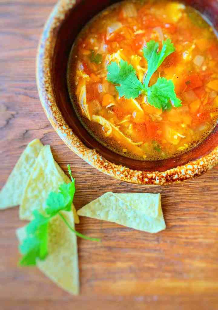 Hot Mexican Chicken Soup on a brown soup bowl with tortilla chips and cilantro