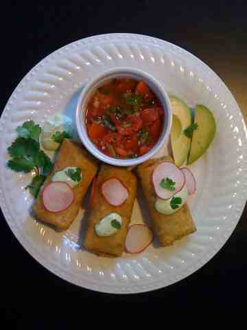 Chicken flautas topped with sliced radishes, avocado cream sauce, cilantro and side of homemade salsa on a white ceramic plate