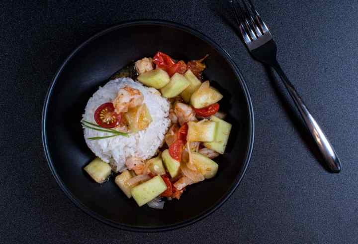 Sautéed Opo Squash with Steamed Rice in a Black Bowl and Fork