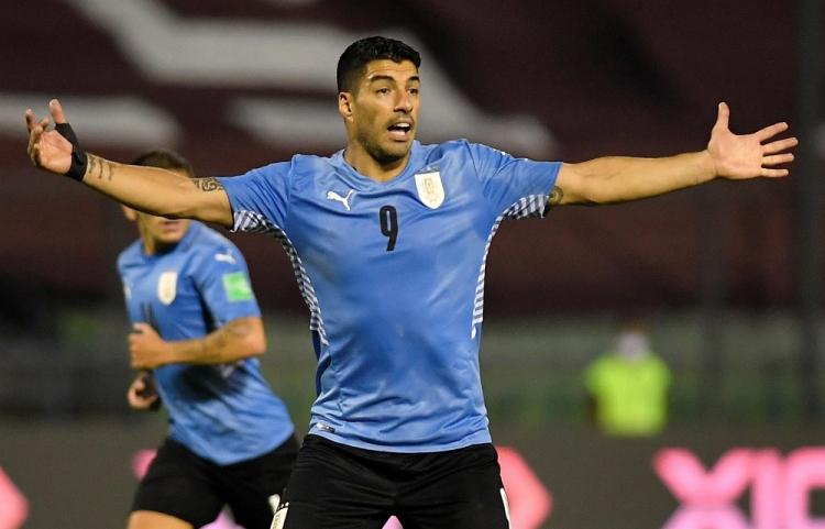 Com camisa azul clara e calção preto, Luis Suárez abre os braços durante jogo do Uruguai