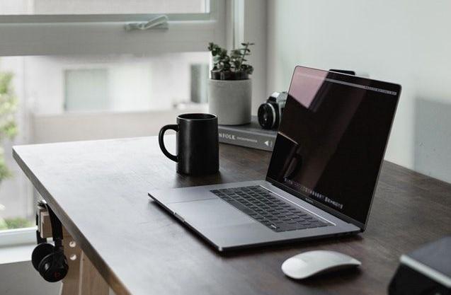 Skrivbord med laptop och kaffekopp i lägenhet
