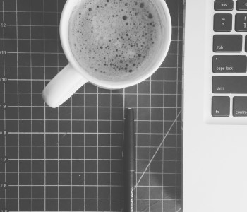 Image of my workspace, coffee to keep me working, and other tools that I use on the daily.