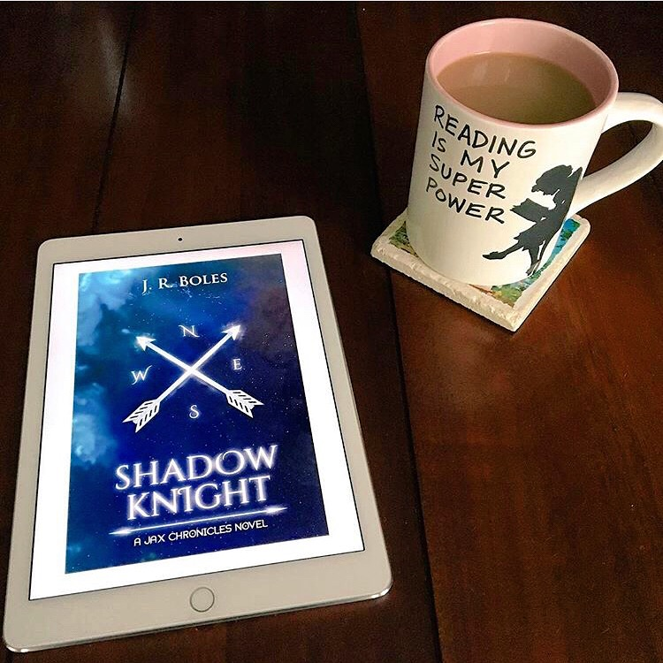 """Alt Text: Image of kindle cover of SHADOW KNIGHT (compass with arrows over blue map with coffee cup showing a woman reading captioned, """"Reading is my super power."""""""
