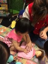 Tucking the baby doll to sleep.
