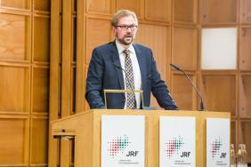 """Dr. Benjamin Schraven, DIE, mit seinem Vortrag """"Die globale Flüchtlingskrise: Trends, Ursachen und die entwicklungspolitische Herausforderung""""."""