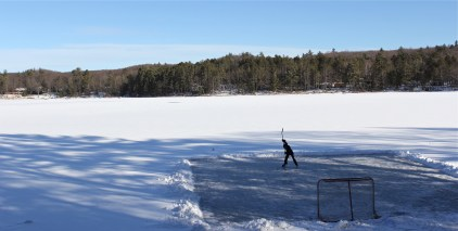 A youth hockey player takes a slap shot on the ice at Heart Lake in Gaylord, Mich.