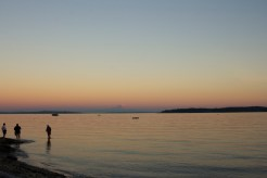 The sun sets over the Puget Sound, with Seattle and Mount Rainier in the distance. This photo was taken from Indianola, Washington.