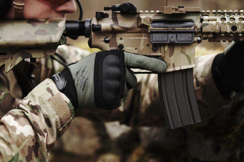 man holding camouflage rifle