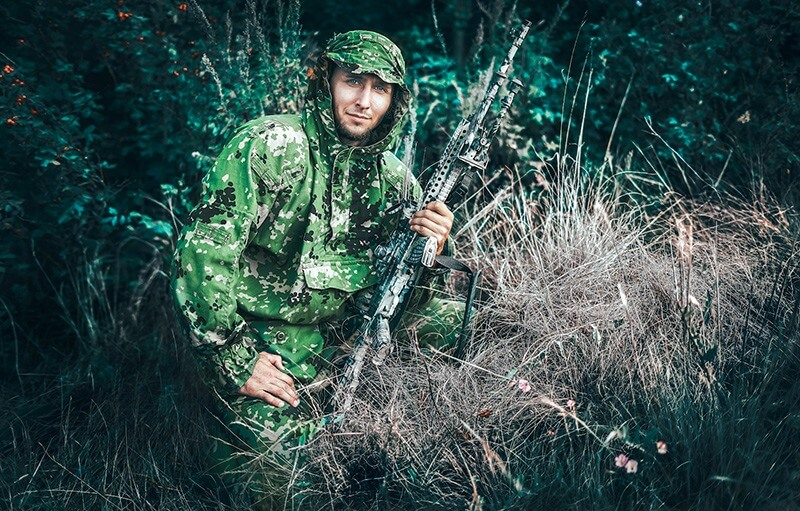 man dressed in camouflage outdoors holding a rifle
