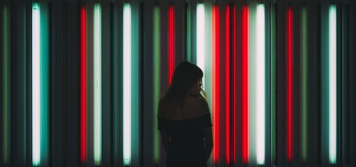 A woman stands in front of neon tubes