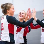 Lena Kindermann high-fives her teammates before a volleyball match-up game.