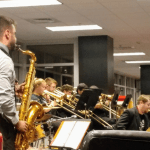 Several members of JSU Jazz Ensemble perform using various instruments. One particular male member is standing in the foreground, with his back to the camera, playing a saxophone.