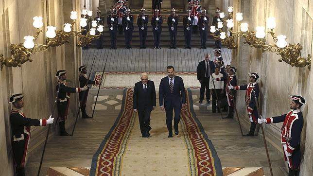 El Rey acompaña, dando su derecha, al Presidente de la República Italiana que por primera ez es recibido en el pie de la Escalera de Embajadores.