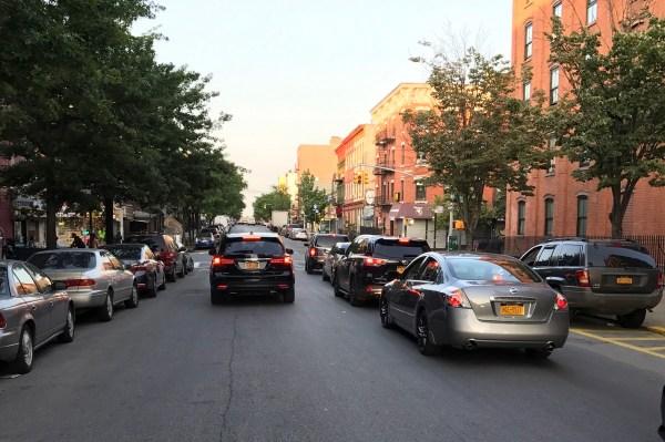 Side-by-side traffic on the single lane on Meserole Avenue.