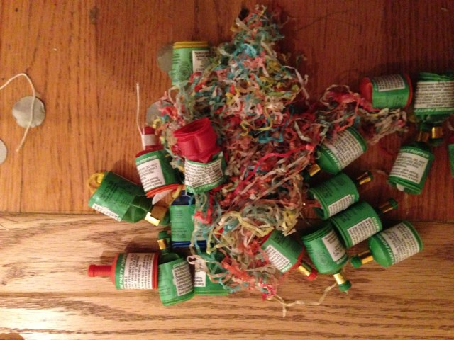 A pile of spent confetti poppers lies on a hardwood floor signaling the end of a festive New Year's Day celebration.