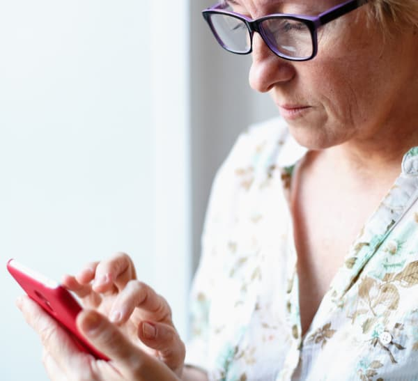 apps to help you budget at midlife+woman-looking-at-phone