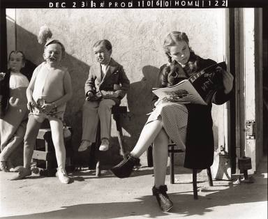 Judy Garland reads Life Magazine outside the sound stages during a break in filming The Wizard of Oz